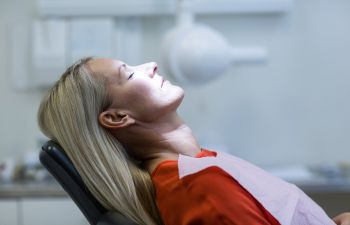 Woman Under Sedation Asleep in Dentist Chair